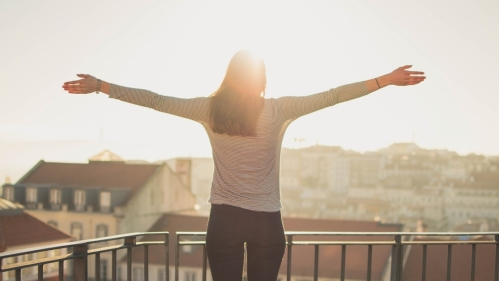 woman standing at balcony with arms spread and sun rising