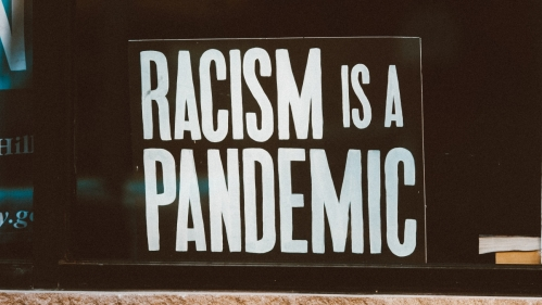 """a black sign sits in a window. On it in big, white, block letters it says """"RACISM IS A PANDEMIC"""""""""""