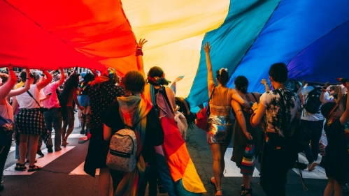 group of people standing under large rainbow parachute who appear to be at a rally or festival
