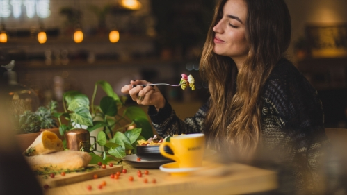 woman holding fork full of pasta eyes closed smiling slightly at a table with a plant and green leaves showing