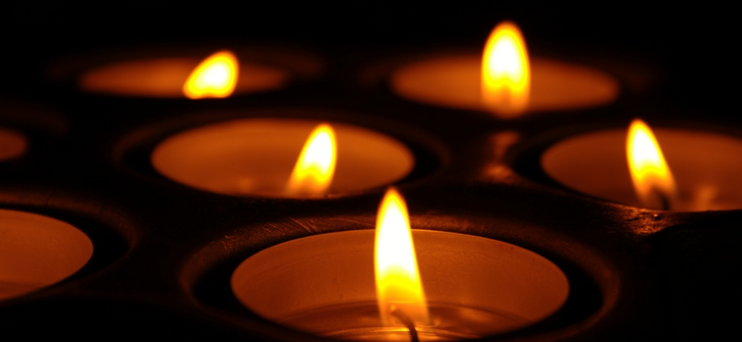 several lit tea light candles in the dark