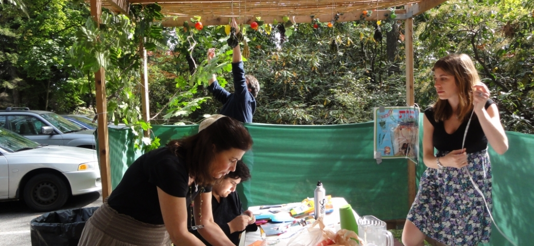 woman wearing white kippah, black t-shirt and gray skirt setting a table inside a sukkah outdoors, while another woman stands nearby and another person is seated at the table