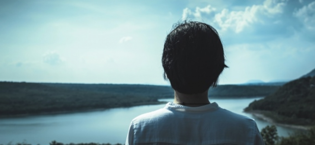 Back of person's head facing a distant lake