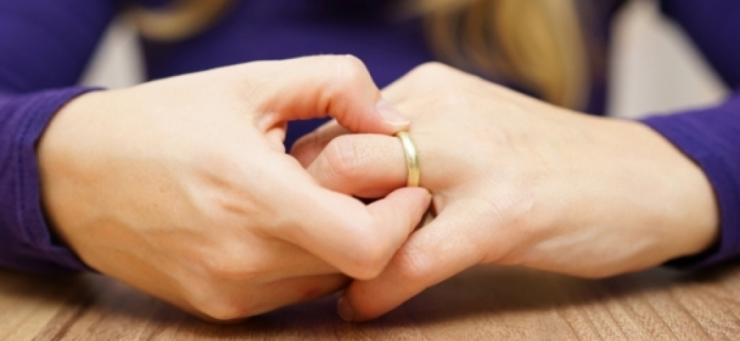 close up of woman's hands taking off wedding ring