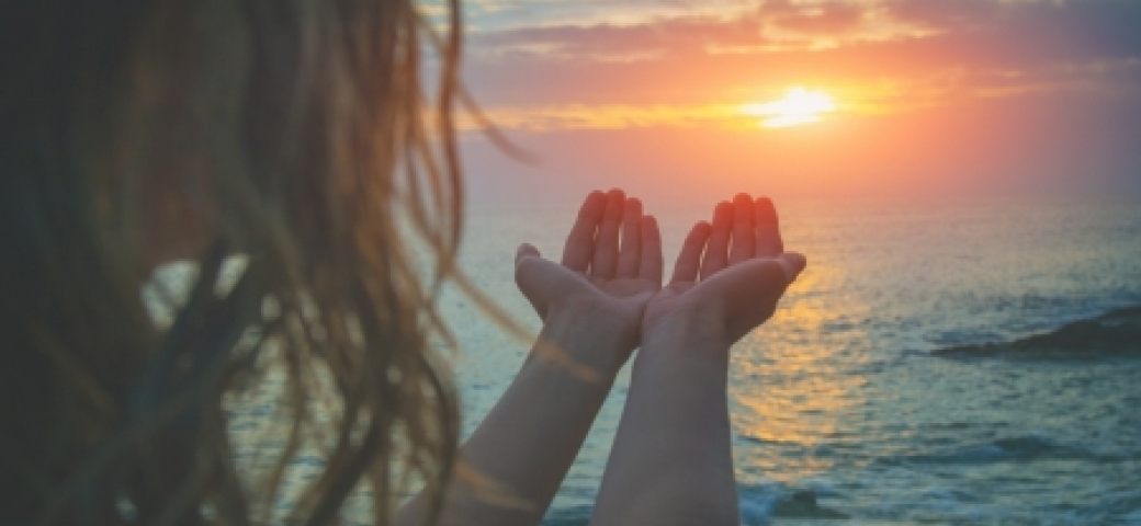 woman holding hands open to sunset over ocean