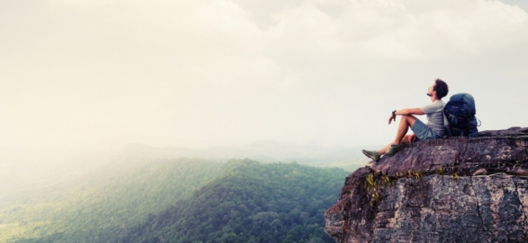 hiker resting on a mountain looking up at a vast sky