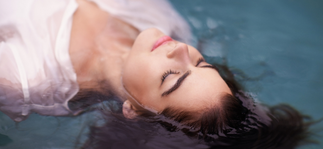 woman with brown hair and white shirt floating in water with eyes closed