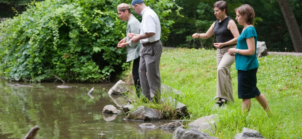 four people, one wearing large kippah, tossing bread crusts in river