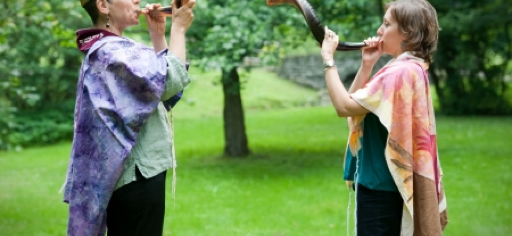 two women wearing colorful tallitot outside blowing shofars
