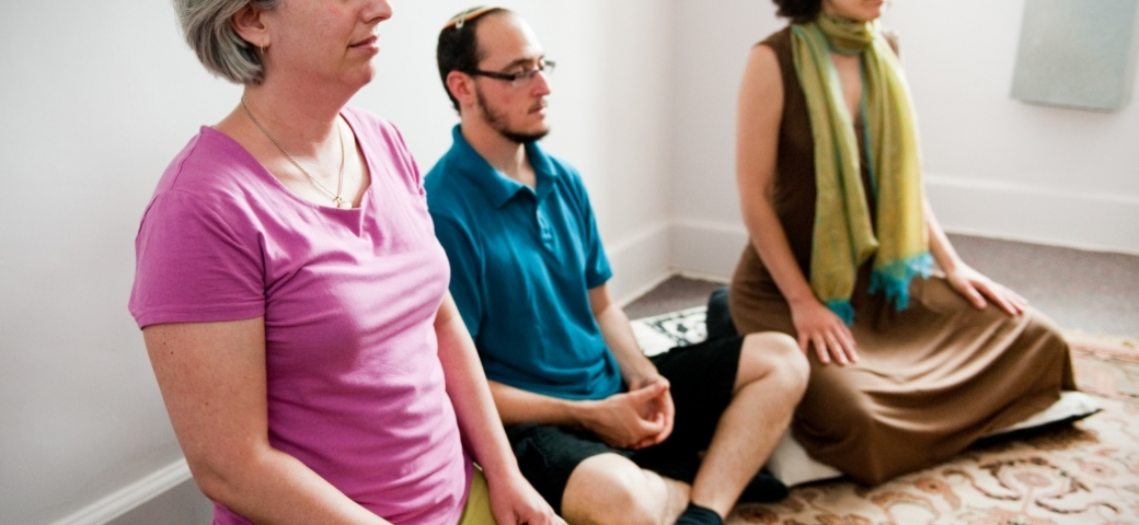 three people in brightly colored clothes meditating in a sunlit room
