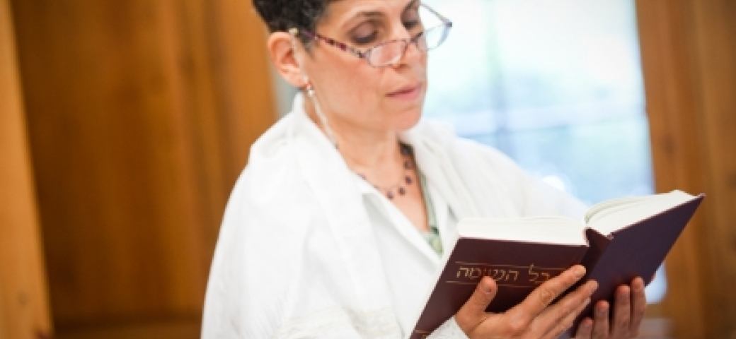 woman in white reading from prayerbook