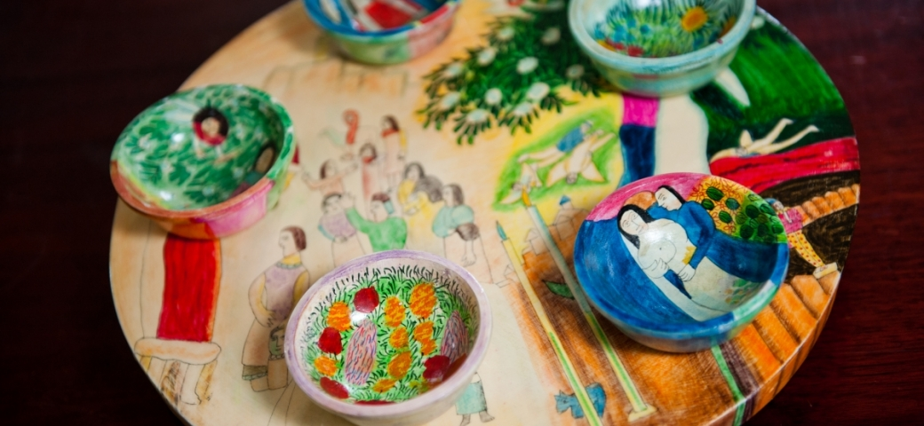 a colorful hand painted seder plate it pictured. Each bowl has different images portrayed.