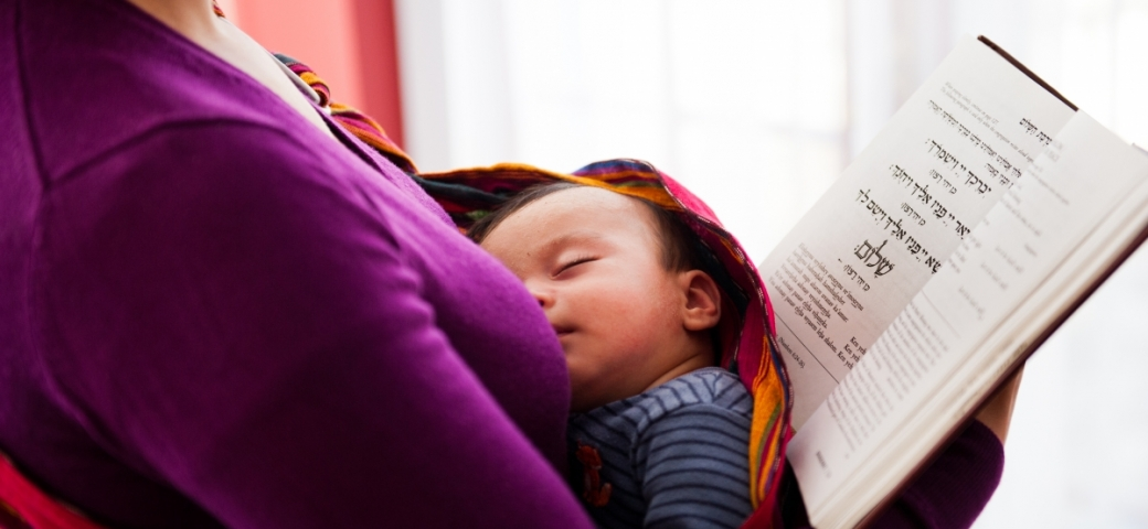 woman in purple sweater holding sleeping baby and siddur open to blessing of children