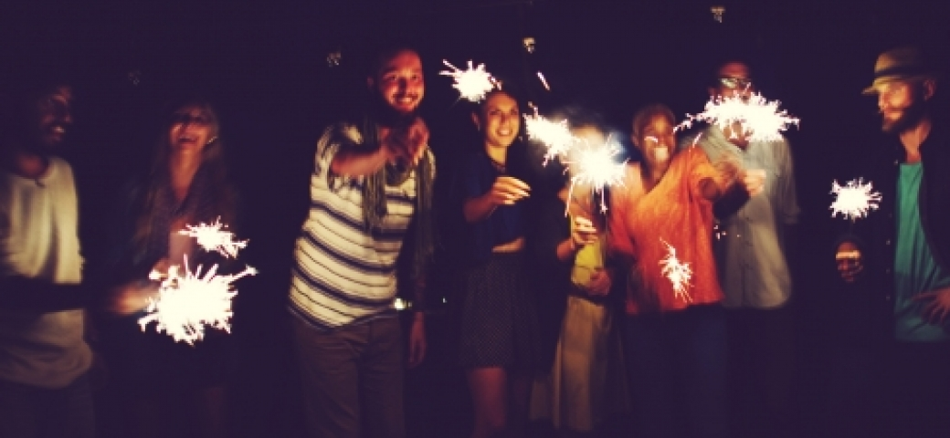 people smiling shining sparklers in the dark