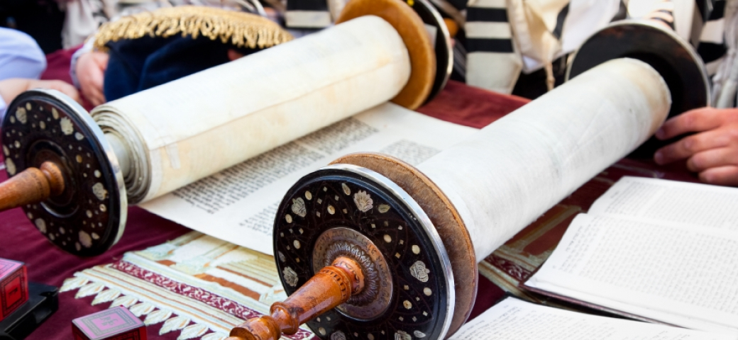 a torah scroll is open on a table covered in red velvet the adornments of the torah are scattered around it and in the background we see people covered in tallit