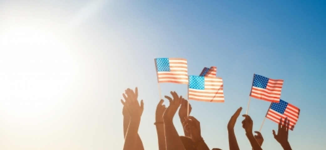 group of people holding small american flags up to the sunshine