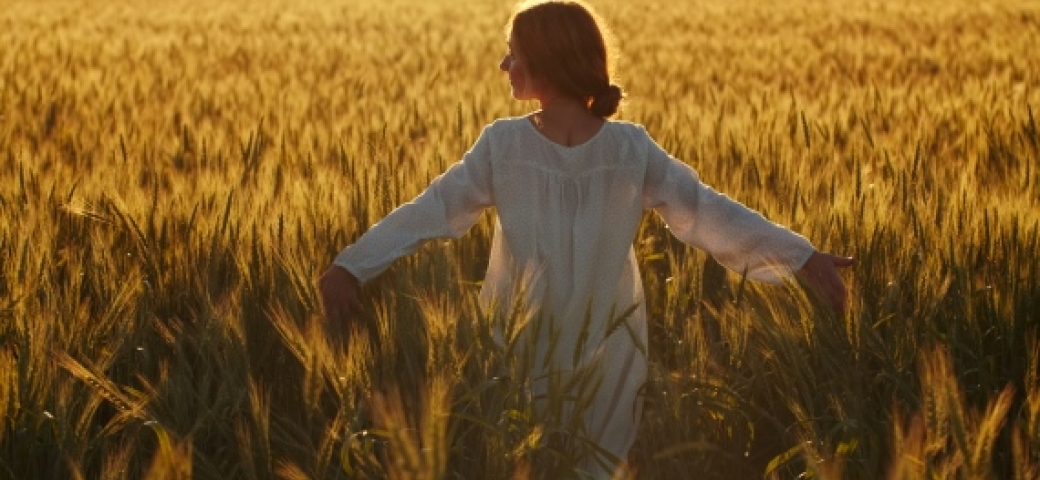 Woman with arms outspread in sunny wheat field