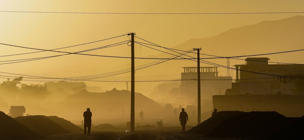 yellow lit photo of electric poles and wires in a dusty area of kabul, afghanistan with mountains barely visible in the background and silouhettes of two people