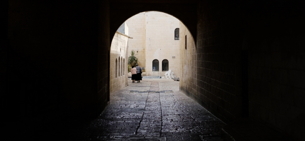 dark archway in jerusalem opening up to lit street with two old women in the distance walking toward building