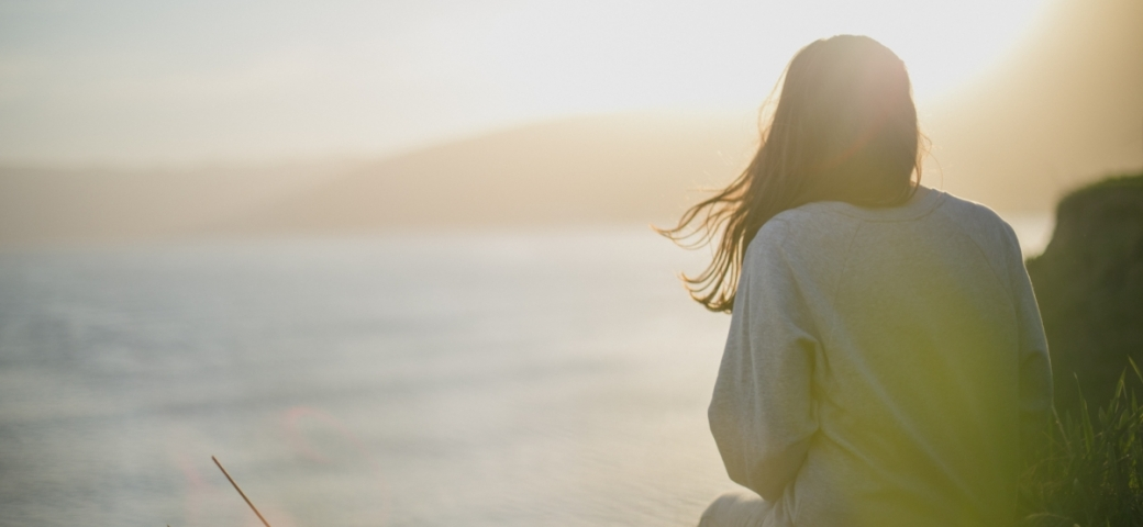 woman shown from behind looking at sea with sunlight
