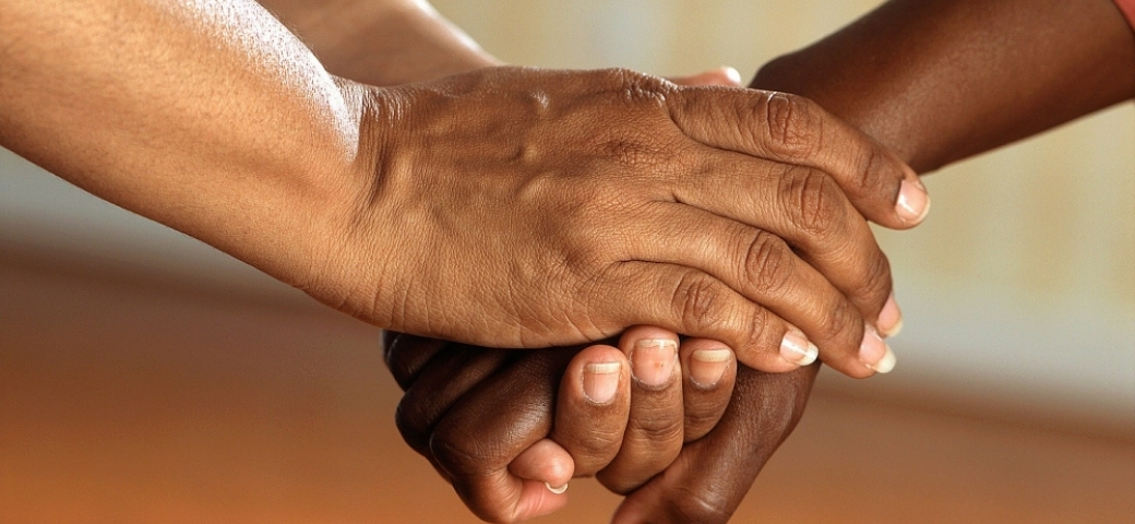 pictured are hands being held from mid-forearm to fingertips. One person is holding the other person's hand in between theres.