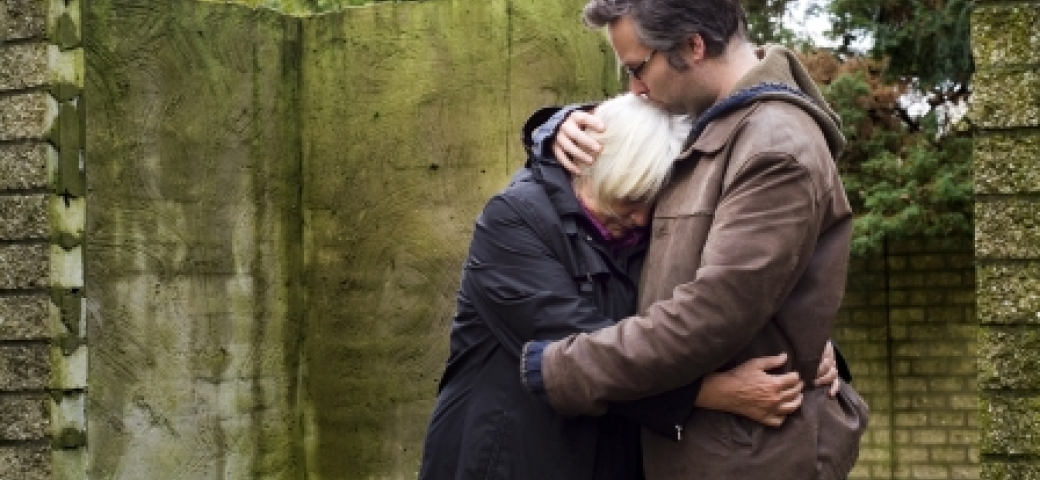 young man embracing older woman at gravesite