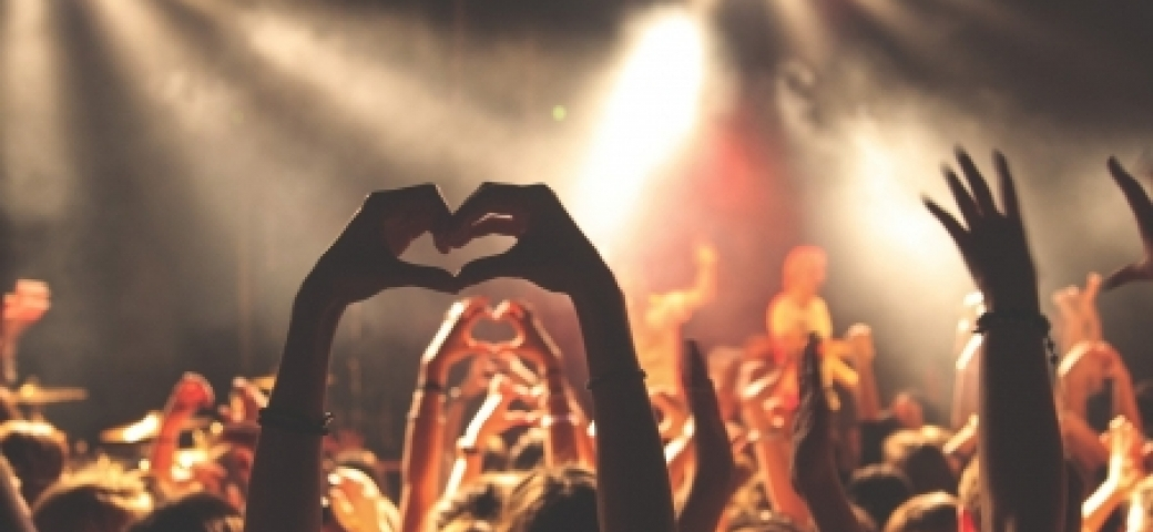 people at a concert with arms lifted and hands forming a heart shape