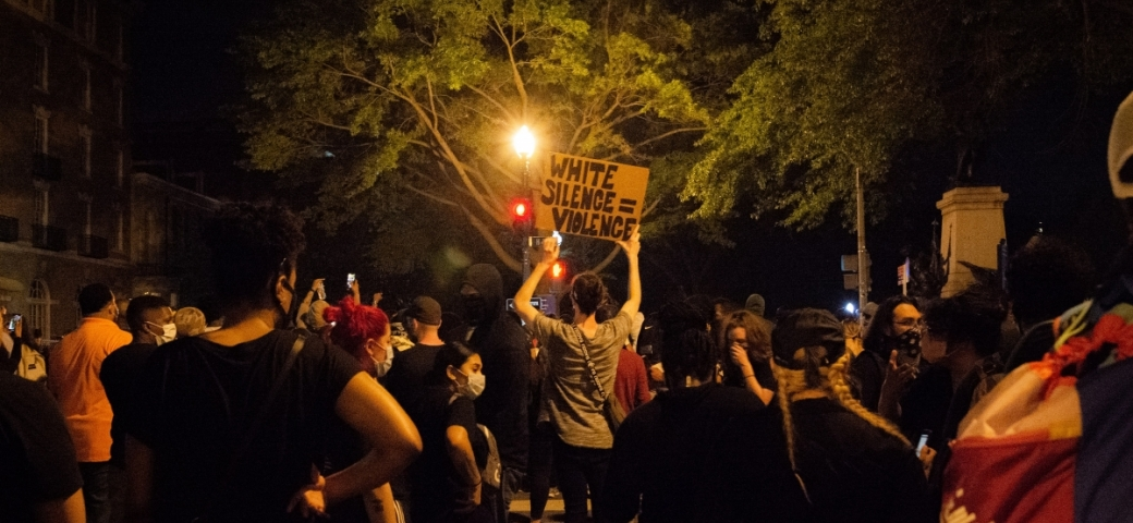 """a protestor stands in the middle of a crowd at night holding a sign that says """"White Silence is Violence"""""""