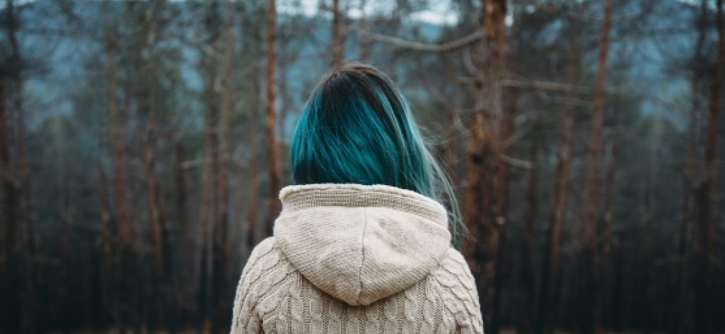 girl with blue hair shown from the back standing before bare trees