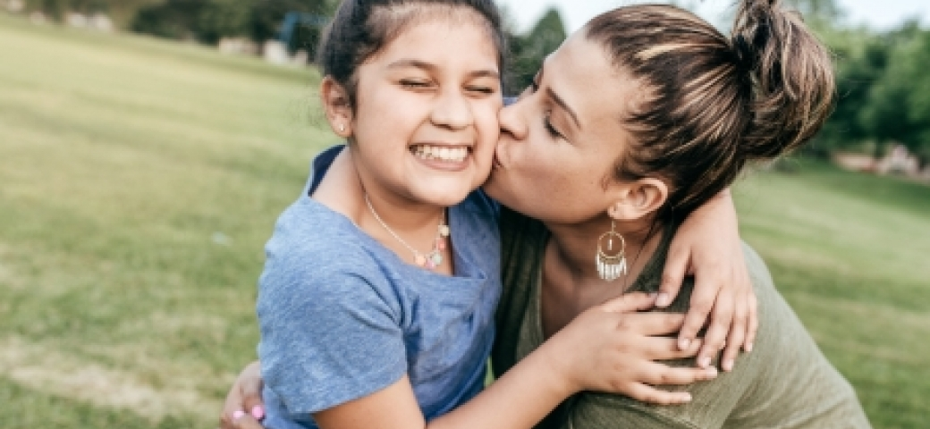 young girl smiling, hugging her mom, as her mom kisses her on the cheek