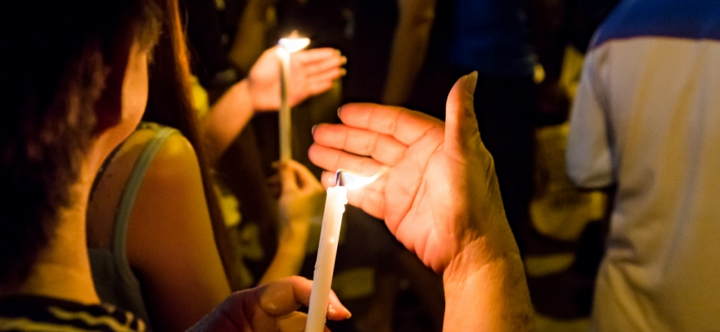person holding candle at vigil