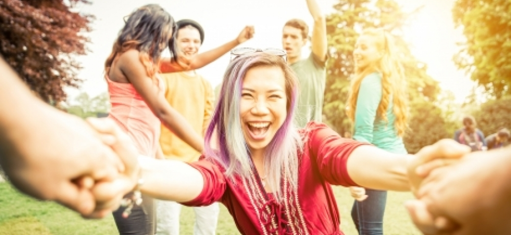 asian woman with purple hair smiling holding hands dancing