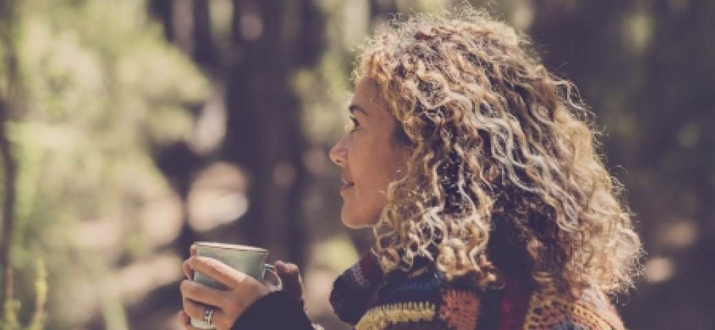 closeup of woman holding mug smiling in the sunlight, trees in the background