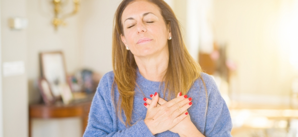 woman with two hands on her heart, eyes closed