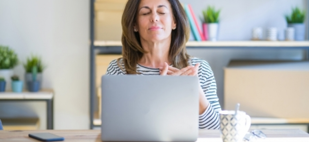 woman with eyes closed, hands on her heart, at the laptop