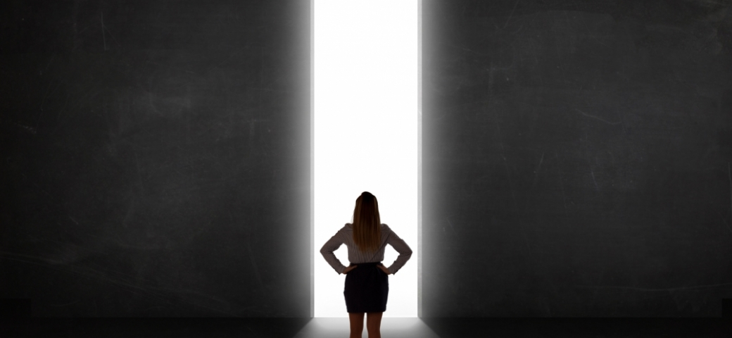woman standing in the center of a room, hands on hips, facing a strip of light. on either side is black darkness.