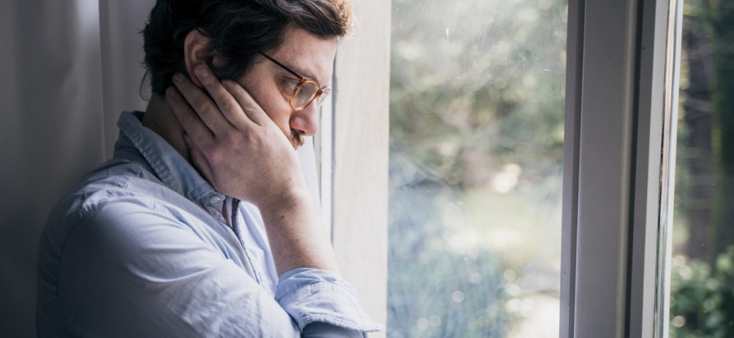 Thoughtful anxious guy looking out the window