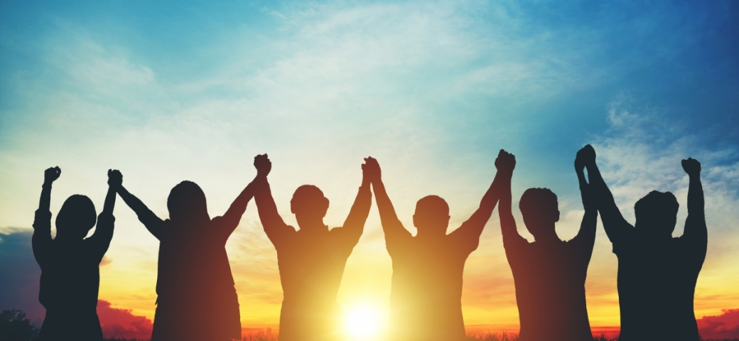 silhouette of group of people holding hands with arms to blue sky and sun shining through