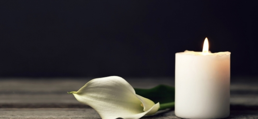 white flower petal next to lit candle