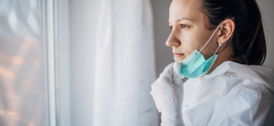 woman looking out window with mask around her chin and gloves on