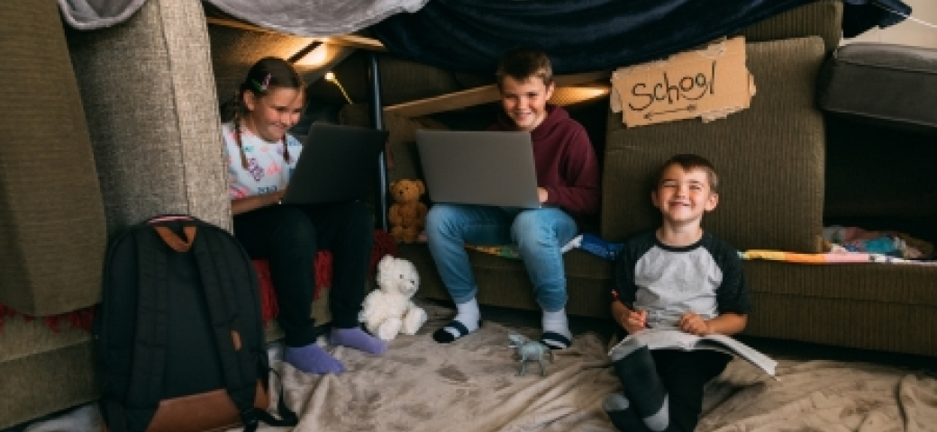 three kids learning in a homemade fort with a cardboard sign that says school