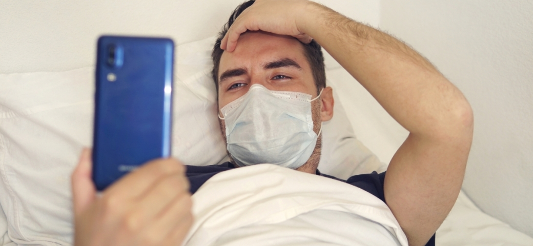 handsome white man wearing mask lying in hospital bed holding phone and smiling