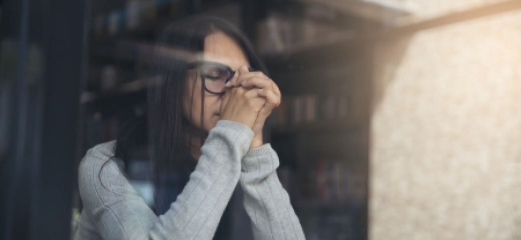 woman at window with eyes closed praying