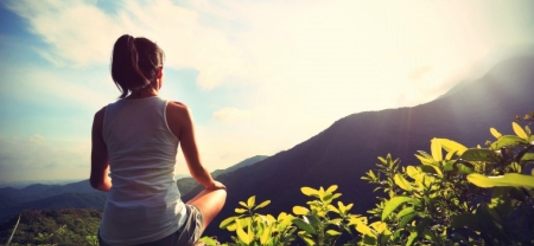 woman sitting in field gazing at mountain with sunlight