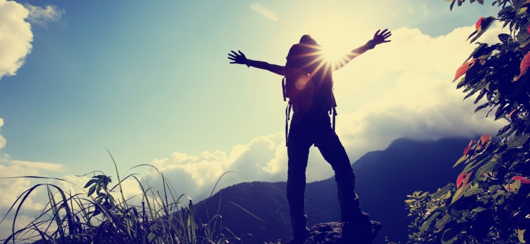 person standing toward the sunshine on a mountain with arms open in a v