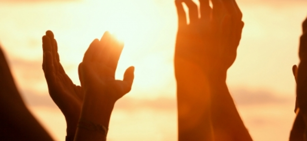 silhouette of hands reaching toward sunlit sky