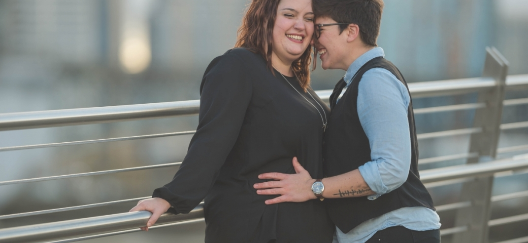 A queer couple stand against a railing, smiling, and embracing