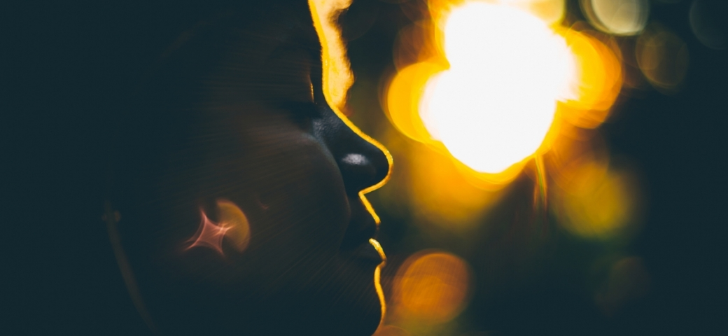 close up of black woman with eyes closed, light streaming from behind