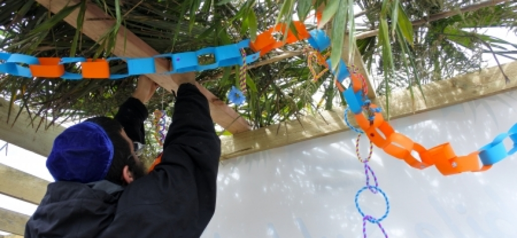 man putting up paper chain in a sukkah