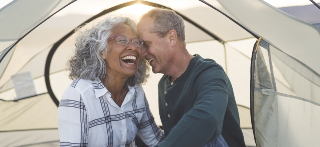 older couple sitting inside a white tent outdoors with sunlight streaming through. The woman is brown skinned with glasses on and gray hair. she is smiling/laughing. Man is light skinned gray haired slightly balding. he is smiling with his forehead pressed to the woman's forehead.
